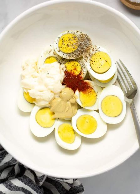 Adding mayonnaise to boiled eggs